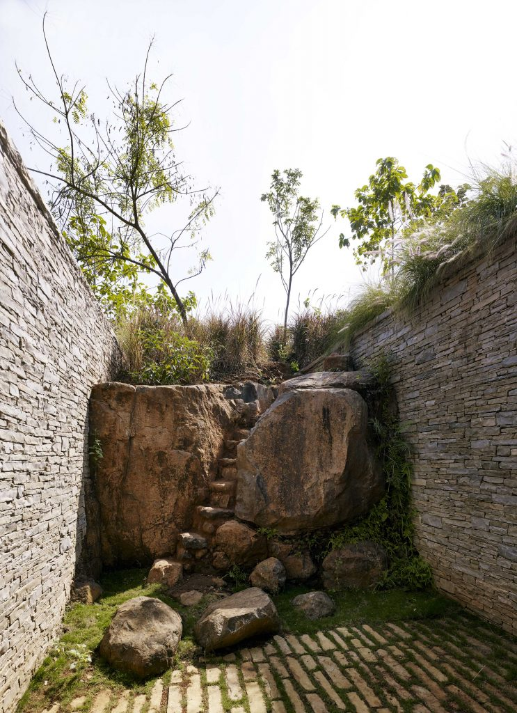 Riparian House nature rock carved courtyard wall